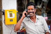 Indian man using a public telephone