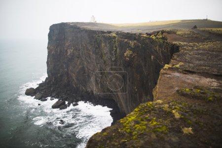 Photo pour Phare dans le promontoire de Dyrholaey sur la côte sud de l'Islande par temps de pluie - image libre de droit