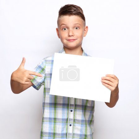 Smiling boy holding finger to blank of papper...
