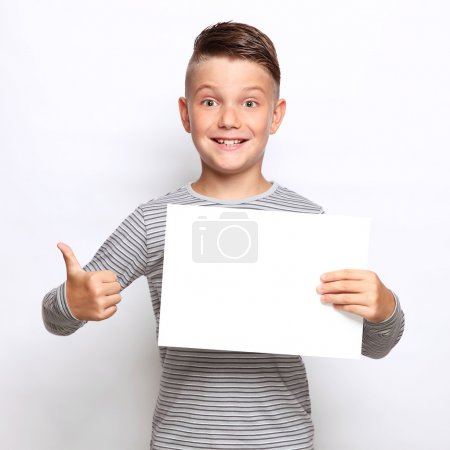 Smiling boy holding blank paper and pointing on it...
