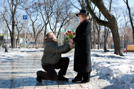 Old-aged man gives flowers to his woman, squatting on one leg