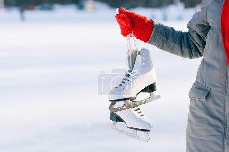 Photo pour Jeune femme montrant de patins à glace pour activité d'hiver patinoire sport en chapeau blanc souriant isolé sur fond blanc - image libre de droit
