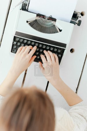 womans hand typing on retro machine