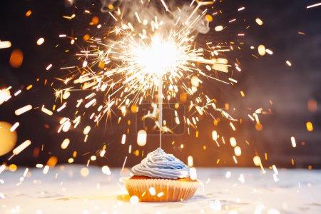 Photo pour Gâteau d'anniversaire avec un scintillement sur un fond bleu . - image libre de droit