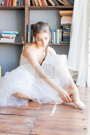 Photo pour Ballet danseuse attacher des pantoufles autour de sa cheville femme ballerine pointe . - image libre de droit