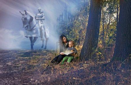 Photo pour Mère et jeune fils lisant des contes de fées près des arbres, derrière eux chevalier sur le cheval et château dans les nuages - image libre de droit