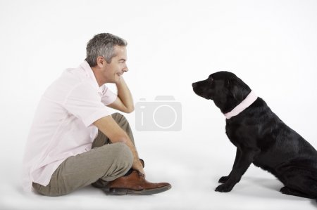 Photo for Middle aged man playing with Black Labrador dog - Royalty Free Image