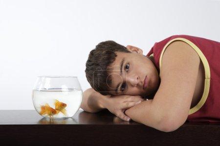 Photo pour Portrait d'adolescent garçon vêtu de vêtements de sport avec poisson dans un bol - image libre de droit