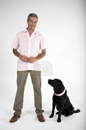 Photo for Middle aged man standing with Black Labrador dog - Royalty Free Image