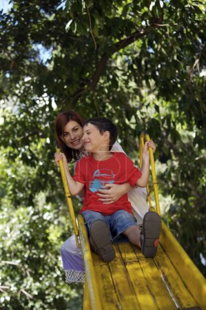 Mother and son on yellow slide