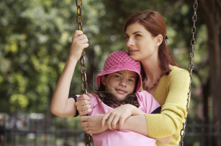 Mother and daughter playing on swing
