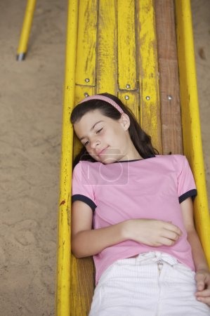 Photo for Small pretty girl lying on old yellow slide on playground - Royalty Free Image