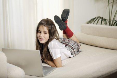 Photo pour Adolescente étudiant avec ordinateur portable dans sa chambre - image libre de droit