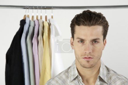 man with row of different shirts
