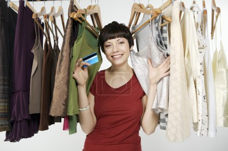 Photo for Attractive young woman holding credit card near hangers with clothing items - Royalty Free Image