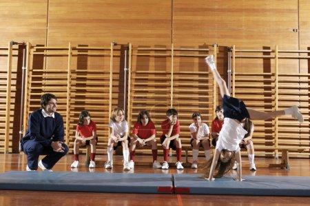 Photo pour Groupe d'enfants faisant de la gymnastique en salle de gym avec professeur - image libre de droit