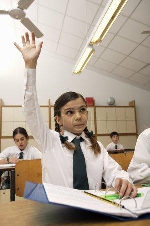 Adorable smart schoolgirl raising hand