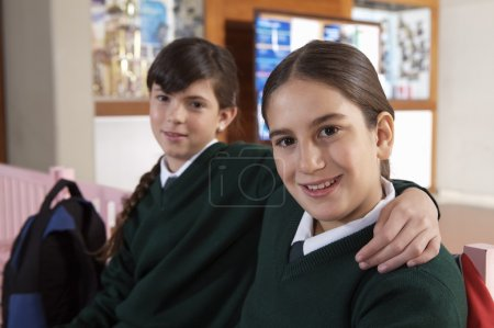 Schoolgirls sitting on bench