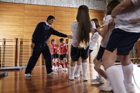 Photo pour Les enfants tirent la corde dans le gymnase scolaire - image libre de droit