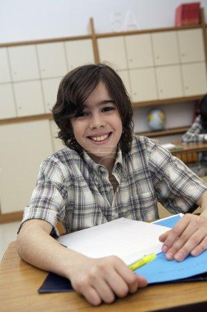 School boy sitting by the desk