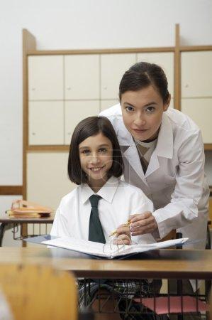 Teacher explaining something to the schoolgirl