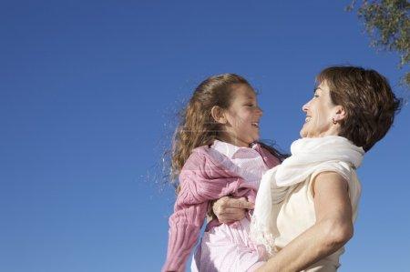 Foto de Abuela con su nieta en el fondo de cielo azul - Imagen libre de derechos