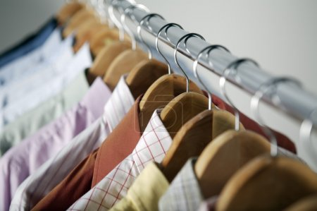 Photo for Row of hangers with different shirts on metal rail - Royalty Free Image