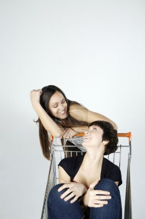 women fooling around with shopping cart