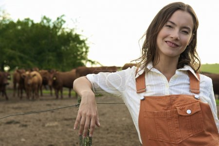 young woman against herd of bulls
