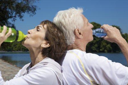 Foto de Pareja macho y hembra adulto después de hacer ejercicio agua potable bckground cielo azul - Imagen libre de derechos