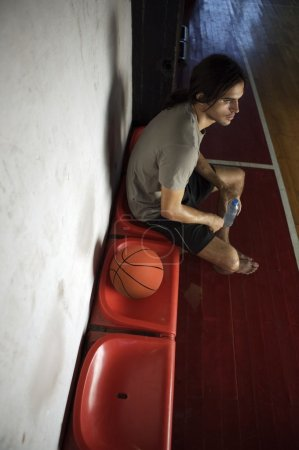 Basketball player sitting in gym hall