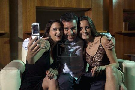 man with two women taking selfie