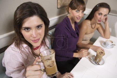 Photo pour Jeunes femmes boire cappuccino à la table du restaurant - image libre de droit