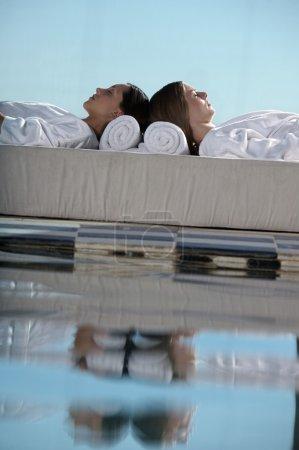 women lying near swimming pool