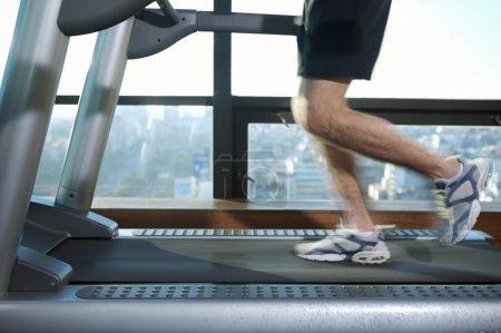 Male legs running on treadmill