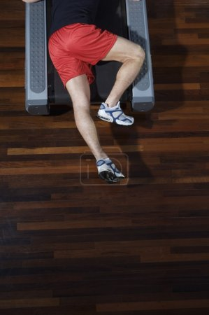 man lying on treadmill