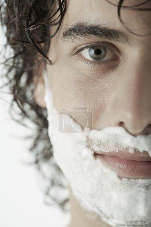man with shaving cream on half his face