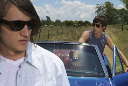 Two males with blue car