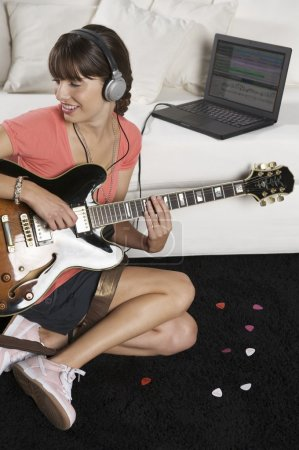 Photo for Attractive teenage girl in pink shirt listening to music from laptop in headphones while playing guitar - Royalty Free Image