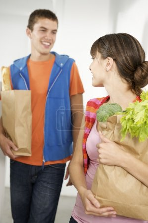 young couple carrying groceries