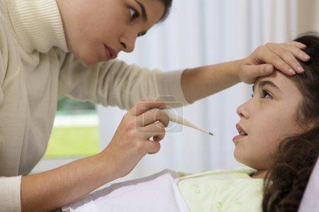 Photo pour Femme, placer le thermomètre dans la bouche de sa petite fille - image libre de droit