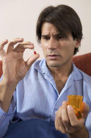 Man inspecting a pill