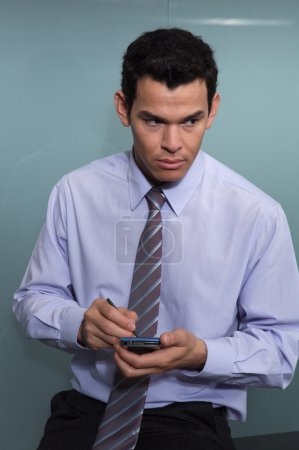 Portrait of businessman using a electronic agenda