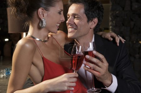 A couple smiling while having cocktails