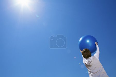 Foto de Una mujer mayor sosteniendo una bola del ejercicio sobre fondo de cielo azul - Imagen libre de derechos