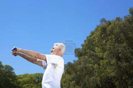 Foto de Un anciano ejercicio sobre fondo de cielo azul - Imagen libre de derechos