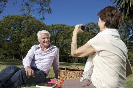 Foto de Feliz pareja en el parque, tiempo de familia, mujer que foto de su marido - Imagen libre de derechos
