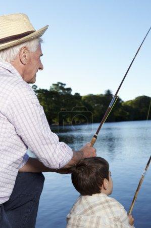 Foto de El niño y su abuelo con cañas de pescar en un viaje de pesca en el fondo del lago - Imagen libre de derechos