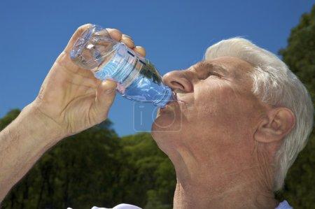 Foto de Un anciano beber de la botella sobre fondo de cielo azul - Imagen libre de derechos