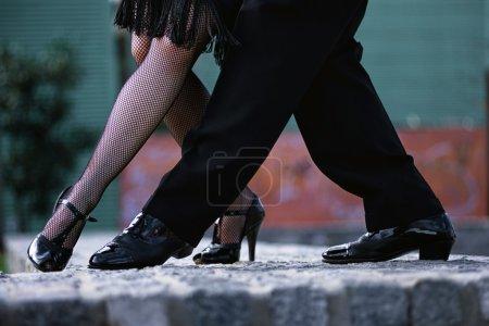 Photo pour Couple latin dansant Tango dans la rue, Jambes d'homme et une femme dans la danse la plus romantique : tango.Tango danseurs en action - image libre de droit